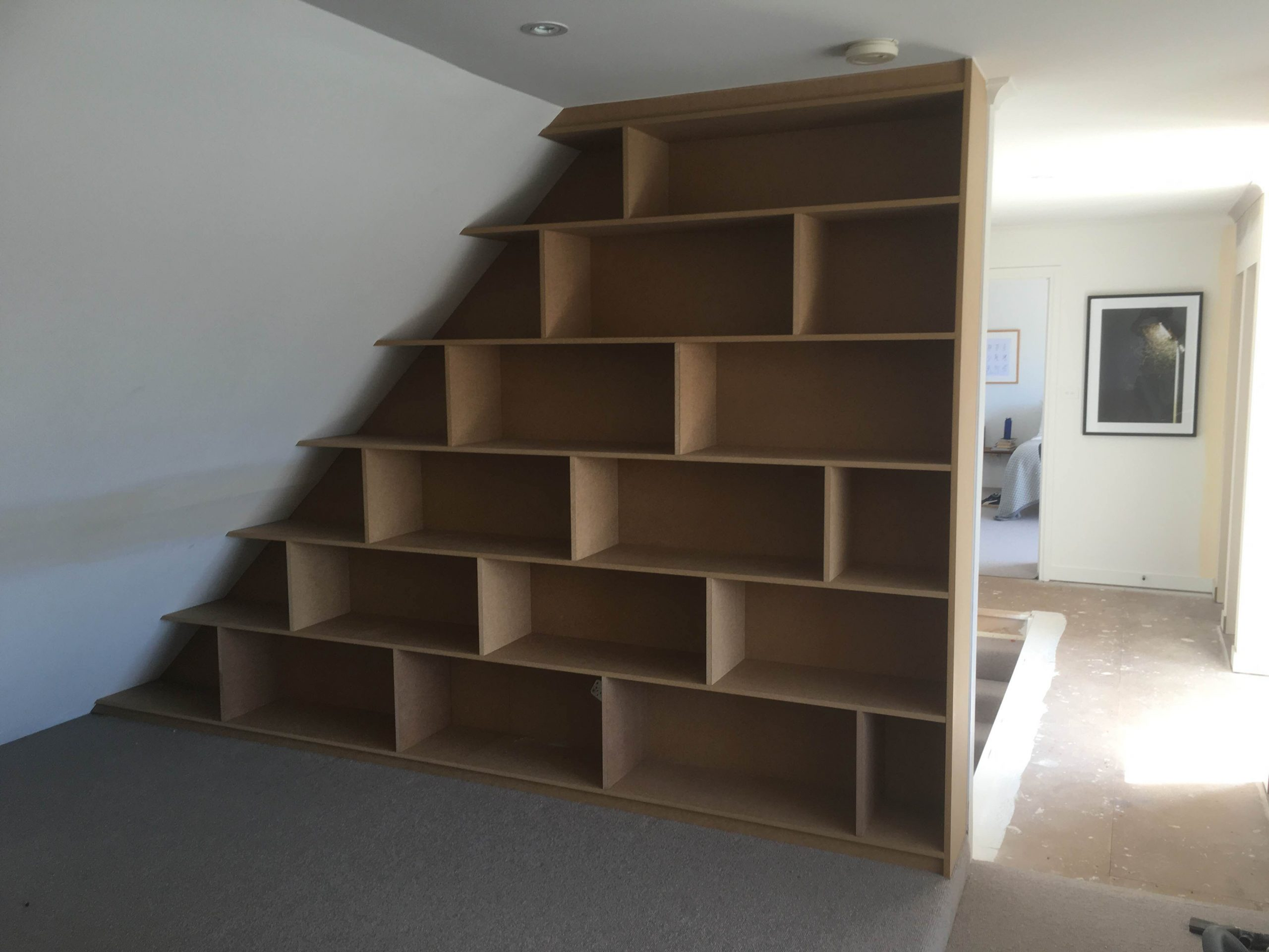 bookshelf under stairs